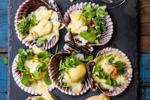 Baked scallops on slate with lemon, cilantro, bread white wine