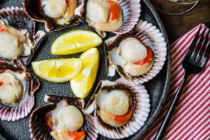 Raw scallops with lemon, cilantro on slate plate, white wine