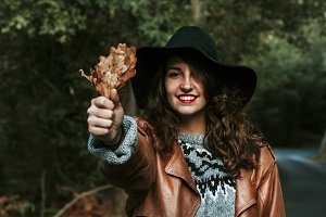 pretty young woman smiling with autumn leaves