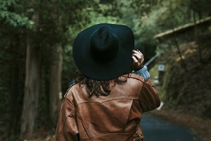 girl with hat walking along the road behind the forest