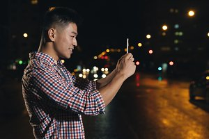 Asian young man taking a picture.