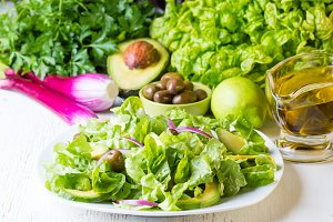 Green salad and ingredients lettuce, avocado, olives, oil, herb onion