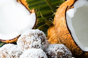Coconut rum balls on green mat of palm leaves