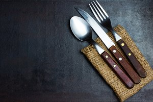Rustic set of cutlery knife, spoon fork. Black background
