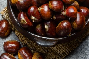 Chestnuts castanas in clay bowl on black background