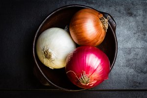 Different colorful onion in clay bowl on black background