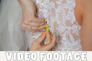Buttoning on the bride's dress