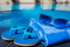 slippers and sunglasses on swimming pool