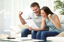 Excited couple reading a letter