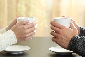 hands of a couple holding coffee