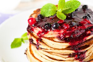 Stack of pancakes topped with berry jam