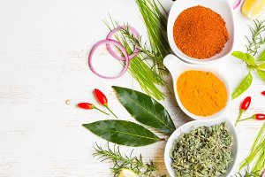 Dry colorful spices in bowls with fresh seasoning on white