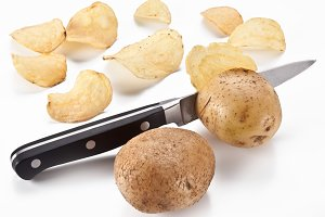 Conceptual image - the knife cuts fresh potatoes and potato chips are obtained.