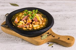 Bean, tomato, bacon and sausage stew with toasted bread