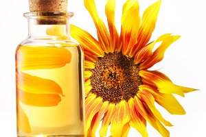 Cooking oil in glass bottle with sunflower on a white background.