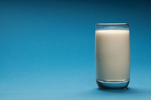 Glass of milk on a blue background.