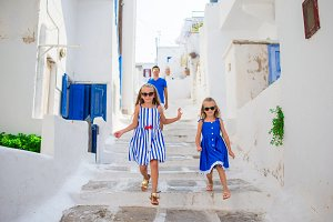 Family vacation in Europe. Father and kids at street of typical greek traditional village on Mykonos Island, in Greece