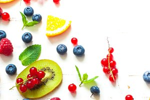 Fresh summer berries and fruits on white