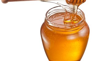 Honey flowing into glass jar.