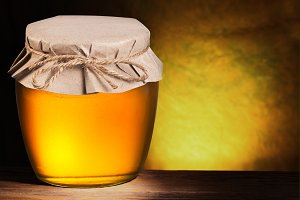 Glass can full of honey over brown