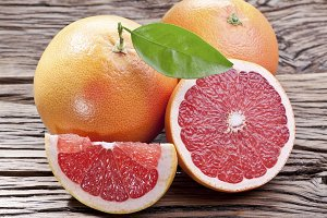 Grapefruits with leaf on a wood