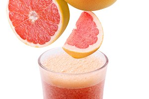 Slices of grapefruit falling into a glass of fresh juice