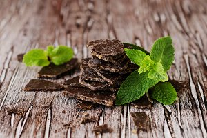pieces of chocolate with mint on wooden background, selective focus