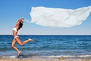 brunette jumping on the beach
