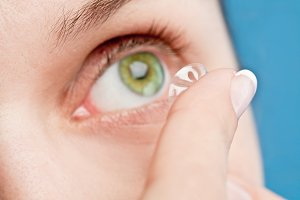human eye with corrective lens on a blue