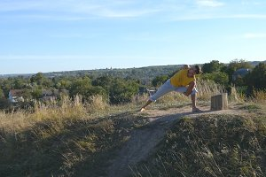 Young man standing at yoga pose at nature. Guy practicing yoga moves and positions outdoors. Athlete doing strength exercise at the hill. Landscape at background. Healthy active lifestyle. Close up