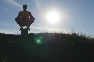 Silhouette of sporty man sitting at yoga pose outdoor. Yogi practicing yoga moves and positions in nature. Athlete warming up his body. Beautiful sky and sun as background. Healthy active lifestyle