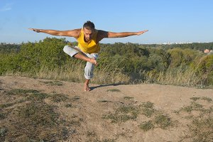 Young sporty man standing at tree yoga pose outdoor. Caucasian guy practicing yoga moves and positions in nature. Yogi balancing on one leg. Beautiful landscape as background. Healthy active lifestyle