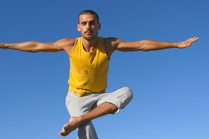 Portrait of young sporty man standing at tree yoga pose with blue sky as background. Caucasian guy practicing yoga moves and positions in nature. Athlete balancing on one leg. Healthy active lifestyle