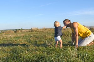 Happy father and son playing on green grass at the field. Family on a summer meadow. Young dad teases his little baby boy in the nature. Spending time together. Close up