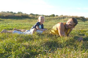 Little child goes at the field to his father, lying on green grass and sit on his back. Happy family on a summer meadow at sunny day. Baby boy walking to his daddy outdoor. Toddler learning to walk.