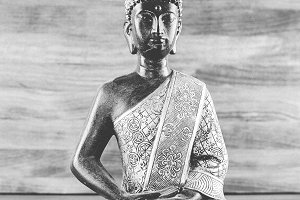 Black and white photograph of a figure of a buddha on wooden background.