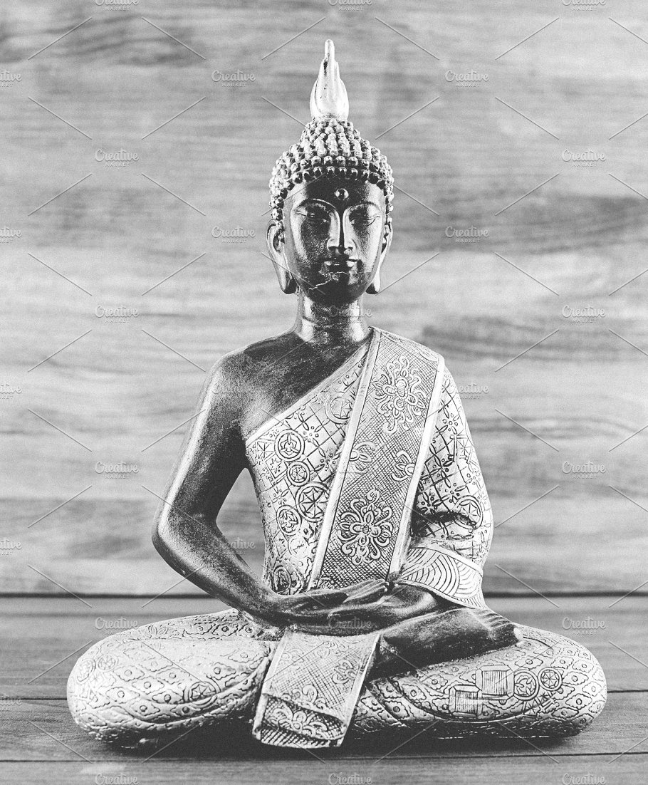 Black and white photograph of a figure of a buddha on wooden background