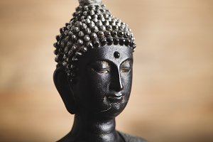 Face of a buddha figure on brown background