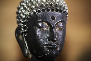 Close-up of the face of a buddha figure on a brown background
