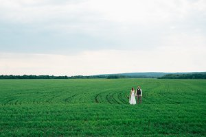 the bride and groom with a bouquet on the green field