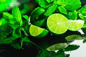 Fresh green mint and lime close-up on a dark background