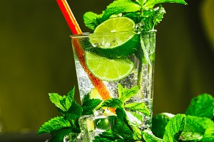 glass of mojito with lime and mint ice cube close-up red straw