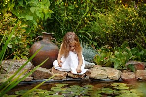 Girl looking into a pond with lilies