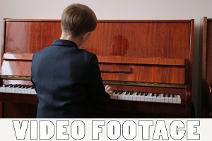 Boy plays piano, back view