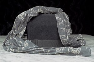Black hat on a grey scarf