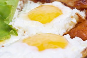 Fried eggs with meat and salad