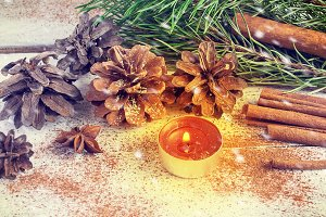Christmas composition with fir cones and candle. snowing