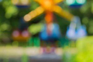Blurred background: Children's Carousel among green trees, bokeh
