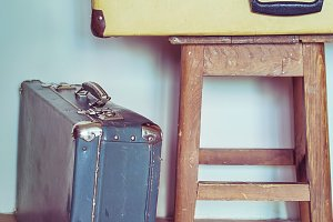 Vintage Composition with old books, suitcases and stool.