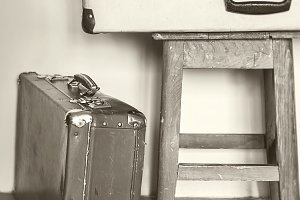 Antique suitcase on a chair and the old books.